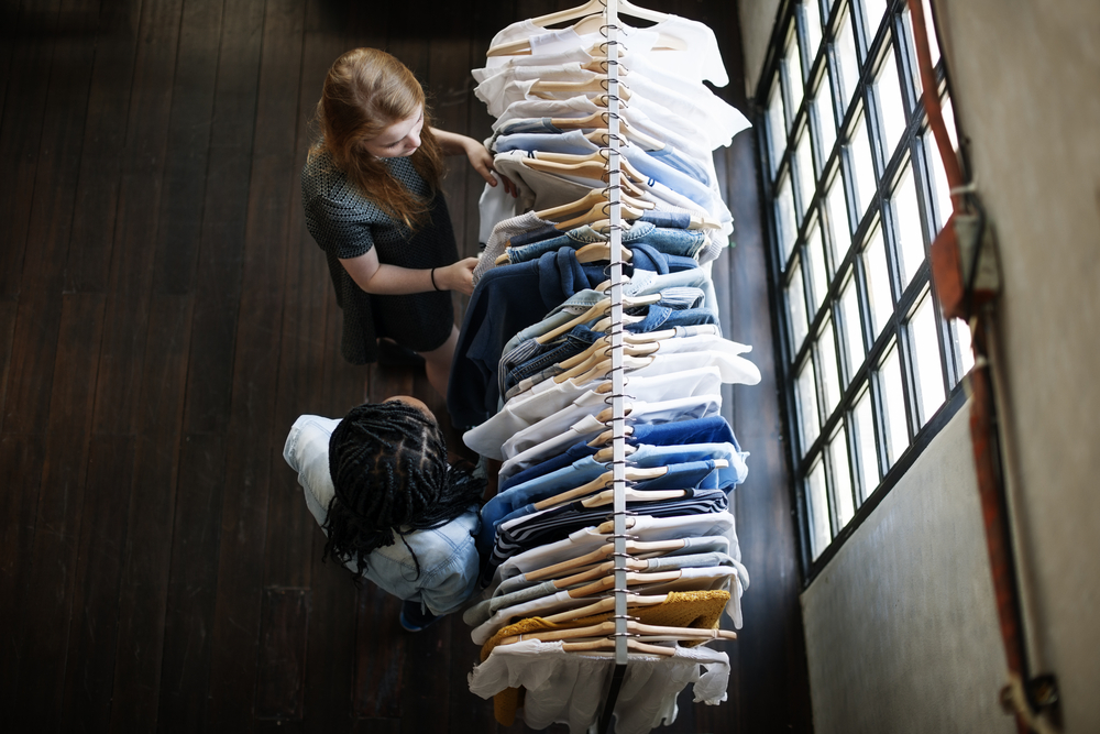 Two people looking through a rack of clothes in a wooden shophouse.